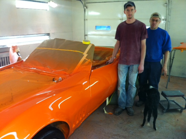Collision Repair Technology student Justin Wise on co-op with Bud Godek standing next to their award-winning orange Corvette.