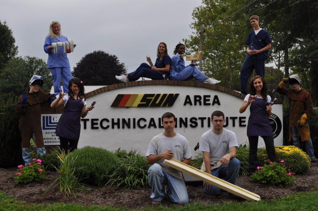Students Pose in Front of Sign