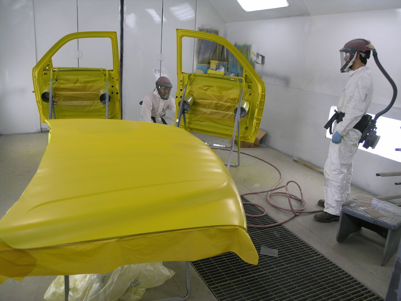 Tyler Spear and Steve Rank painting the doors for a truck being refinished for the City of Sunbury.