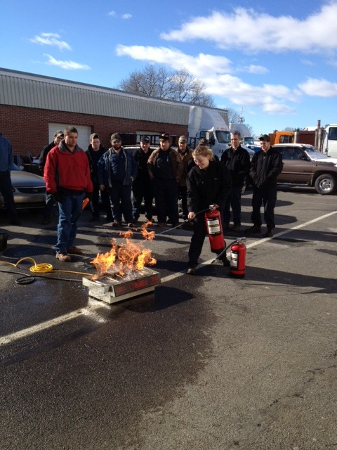 Grace Juliano of Auto Tech Trains with a Fire Extinguisher