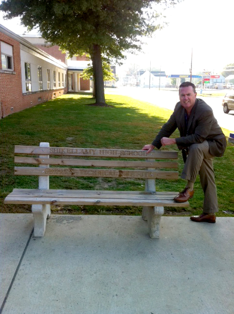 Mr. Weisser poses with the bench after delivery to Shikellamy High School.